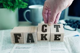 Fake Or Fact On Wooden Blocks On Newspaper, Real News Or Fake News Concept