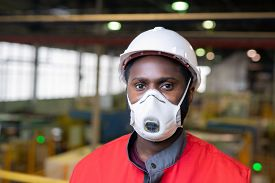 Horizontal head and shoulders portrait of unrecognizable Black male factory engineer wearing protective mask looking at camera