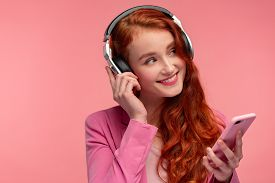 Enjoy Listening To Music. Beautiful Young Redhead Woman With Headphones Listening Music On Smart Pho