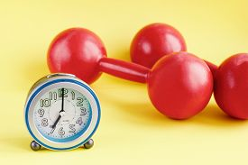 Time For Exercising Concept. Alarm Clock And Red Dumbbell With Colorful Background. Morning Fitness