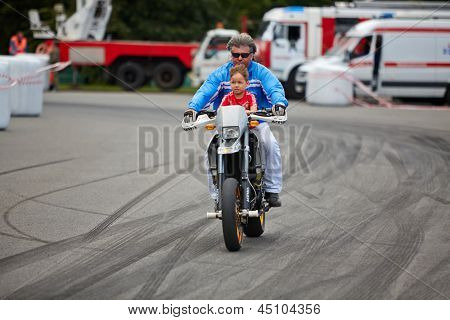 MOSCOW - JUN 30: Member from stuntmen team Avtorodeo Togliatti Trick rides motorcycle with child during Speedfest at Olympic complex Luzhniki, June 30, 2012, Moscow, Russia.