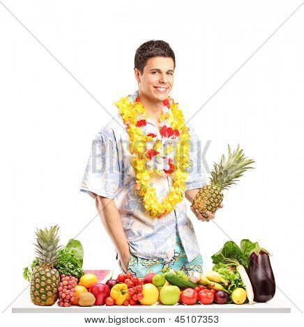 Young man holding a pinneapple and posing behind a table with fruits and vegetables