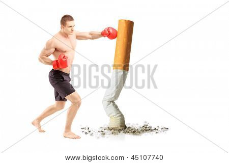 Full length portrait of a male athlete with boxing gloves, punching a cigarette against white background