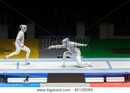 Battle of athletes on championship in fencing.