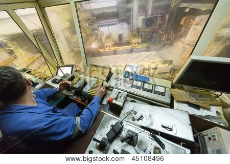 Worker looking on the left in control cabin of rolling mill.