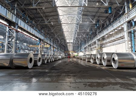 Rows of rolls of aluminum lie in production shop of plant.