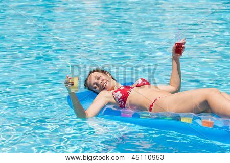Woman swimming in the pool on an inflatable mattress with a drink in in each hand