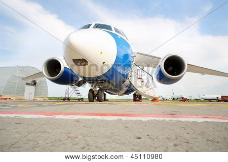 Large white-blue passenger airliner at airport at background of cloudy sky.