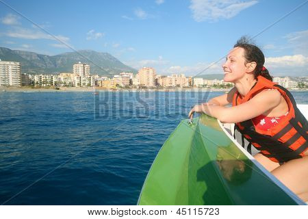 A smiling girl in a boat in the lifejacket admiring views of the coastline, focus on the girl.