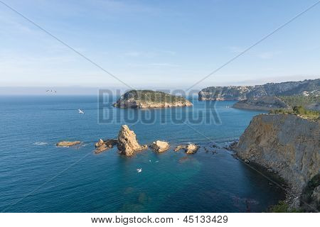 Abrupt Javea coastline at Portichol bay with its landmark island in the background poster