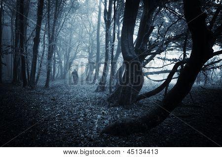 Strange man walking in a dark spooky forest on halloween