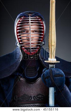 Portrait of kendoka with wooden sword. Japanese martial art of sword fighting
