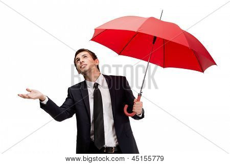 Palming up business man with opened opened umbrella checks the rain, isolated on white