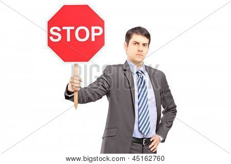 A businessman holding a stop sign isolated against white background