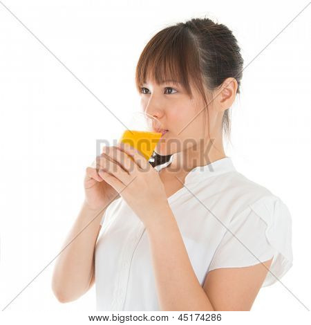 Young Asian woman drinking orange juice, isolated on white.