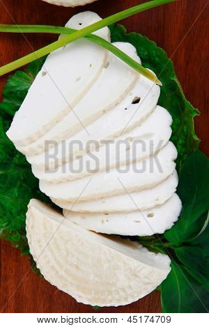 mediterranean dairy  : fresh raw white soft greek feta cheese round and slices on wooden plate isolated over white background