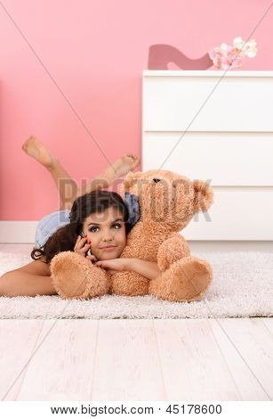 Hübsches Mädchen Handauflegen Stock, umarmt riesigen Stofftier Bär, talking on Mobile Phone.