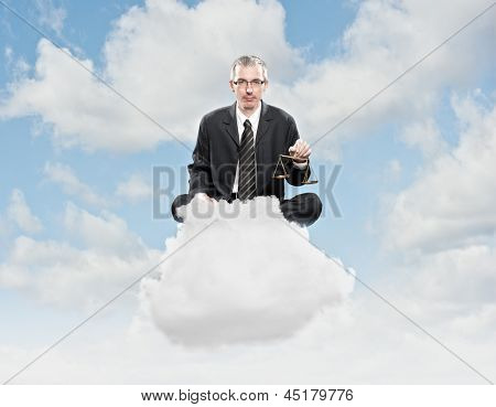 businessman holding justice scale sitting on a cloud