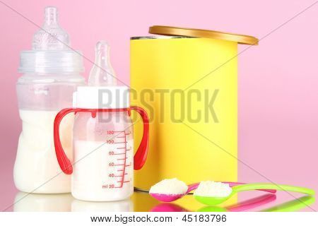 Bottles with milk and food for babies on pink background