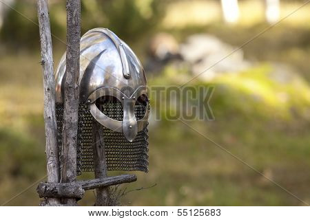 Steel Viking Knight helmet hangs on a wooden fence. Fuzzy background. poster
