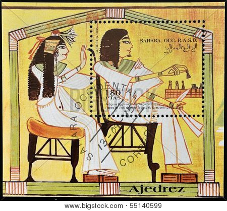 A stamp printed in Sahara OCC. R.A.S.D shows ancient Egyptians playing chess