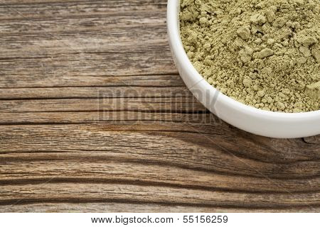 kelp powder nutritional supplement reach in Iodine, Calcium, Iron, Potassium, Vitamin B1, B2, B12 and polysaccharides - ceramic bowl on grained wood