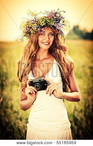 Portrait of a romantic smiling young woman in a circlet of flowers standing with her old camera outdoors.