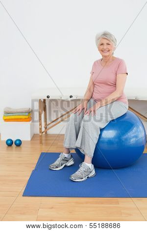 Full length portrait of a senior woman sitting on fitness ball in the hospital gym