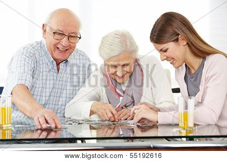 A young social worker solving jigsaw puzzle with senior couple at home