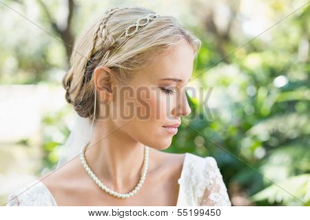 Blonde bride wearing pearls in the countryside