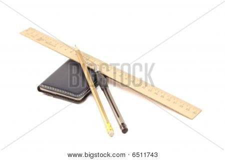 wooden ruler notepad pencil and pen