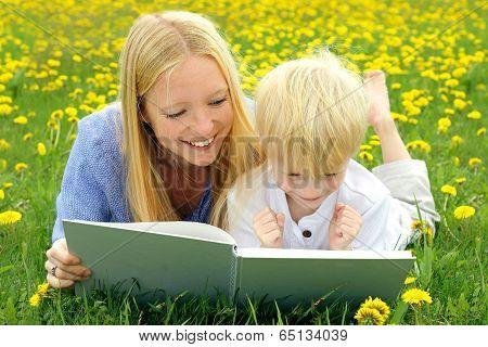Happy Mother And Child Reading Book Outside In Meadow
