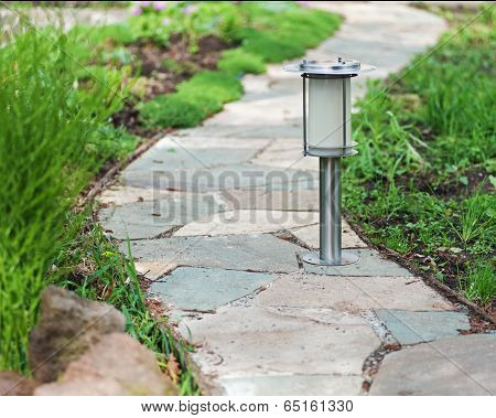 Solar-powered Lamp On Garden Background.