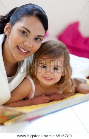 Close-up Of A Beautiful Little Girl And Her Mother Reading A Book