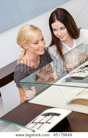 Two girls looking at window case with jewelry at jeweler's shop. Concept of wealth and luxurious life