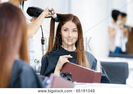 Reflection of hairdresser doing haircut for woman in hairdressing salon. Concept of fashion and beauty