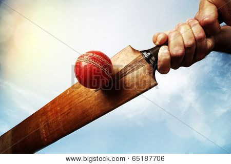 Cricket batsman hitting a ball shot from below against a blue sky