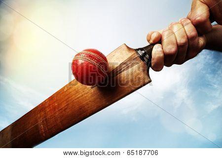 Cricket batsman hitting a ball shot from below against a blue sky poster