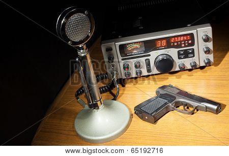 Black handgun on the table with a microphone for a two way radio poster