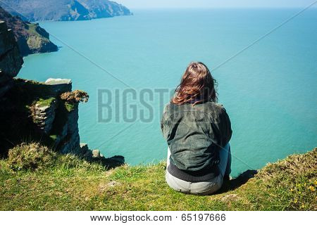 Young Woman Sitting On Edge Of Cliff