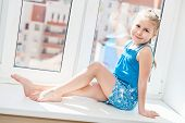 Jouful young girl in blue dress posing on window sill poster