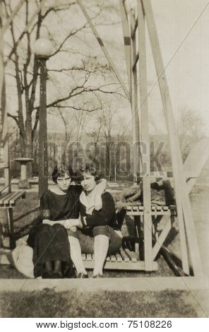 CANADA - CIRCA 1930s: Vintage photo shows Two young girls sitting on a bench in the park.