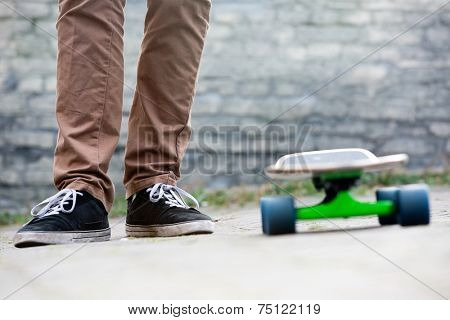 The two feet of a casually dressed man standing next to a skateboard in an urban setting, with a brick wall in the background. All earthy tones