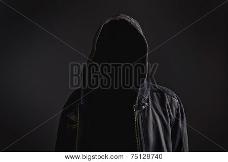 Faceless unknown and unrecognizable man withouth identity wearing hood in dark room spooky criminal person. poster