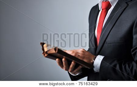 Businessman in a suit holding a book