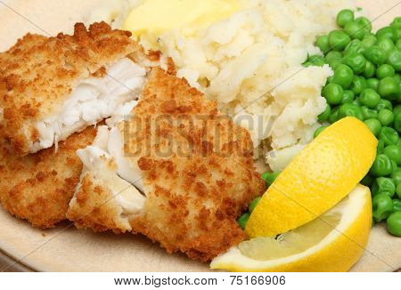 Breaded haddock fish fillets served with peas and mash