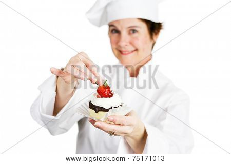 Closeup of a pretty baker holding a delicious strawberry chocolate cheesecake tart.  Shallow depth of field with focus on the strawberry and the tart.