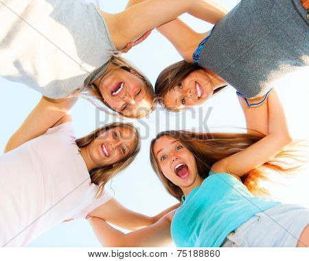 Group of Four Teenage Girls having fun outdoors. Friendship concept. Group of smiling friends staying together, looking at camera and laughing over blue sky. Joyful girlfriends making a huddle