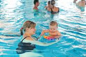 Little baby boy and his mother learning to swim in an indoor swimming pool. Having fun together. Baby swimming concept. poster