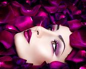 High Fashion Vogue style model portrait with rose petals. Fashion art glamour Woman portrait with bright violet make-up and flowers petals round face. Holiday makeup poster